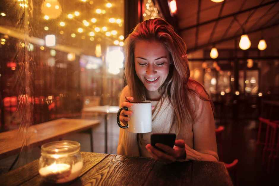woman holding white ceramic mug looking at her cellphone